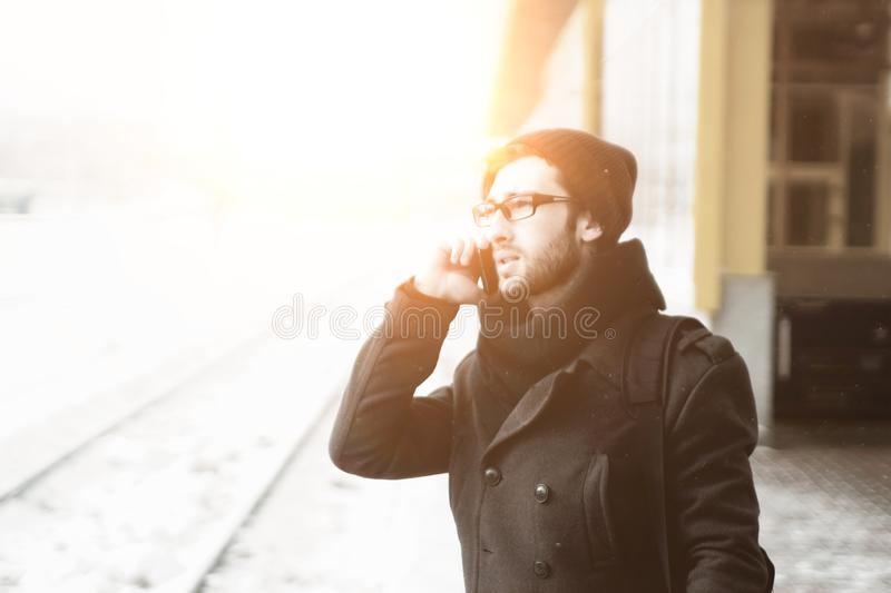Modern man talking on a mobile phone on the street in the winter day stock image