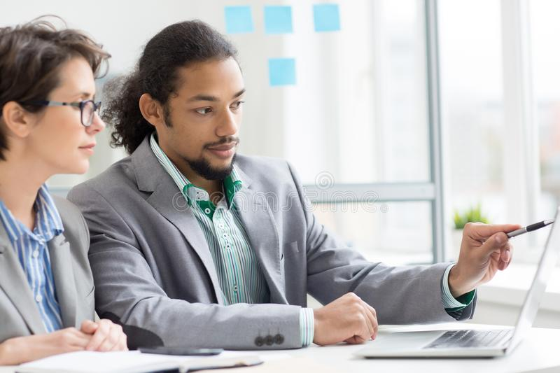 Business strategy. Modern managers looking at laptop display while one of them making presentation of his project stock photography
