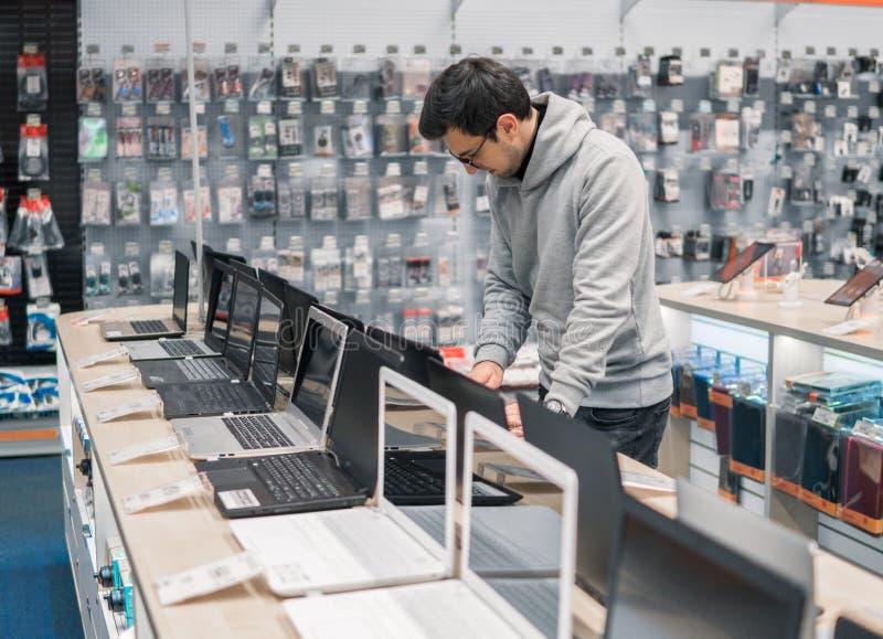 Modern manlig kund som väljer bärbara datorn i datorlagret fotografering för bildbyråer