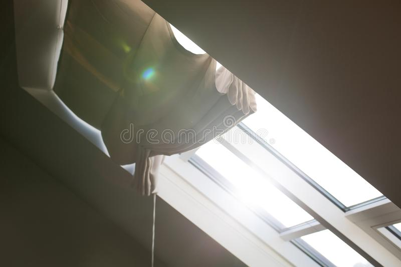 Modern mansard window with blinds in an attic room with sun light. And glare stock photography