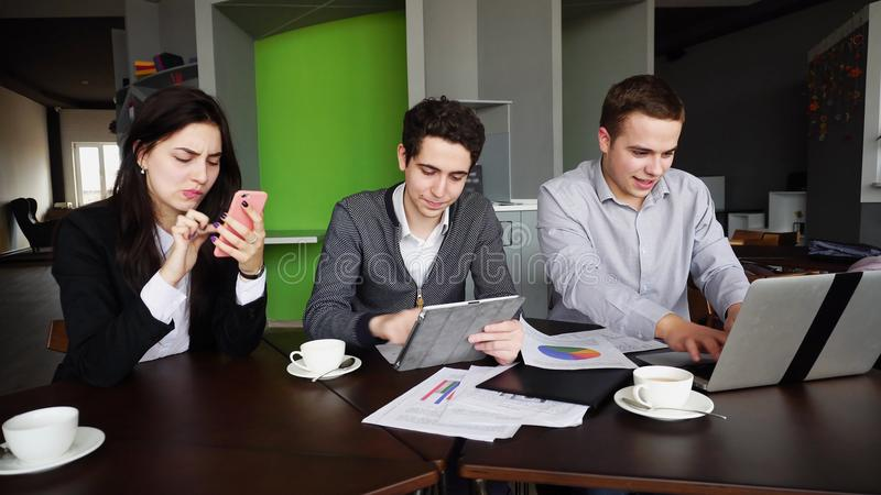 Modern marketers, two men and woman are inundated with things an stock photos
