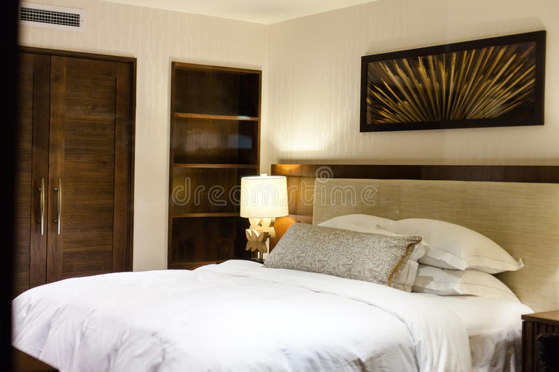 Modern master bedroom. A modern master bedroom. Queen sized bed with white covers stock photography