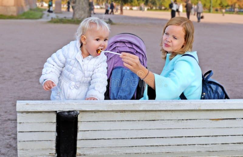 Modern matar den lilla dottern på bänk i trädgårdar royaltyfri fotografi