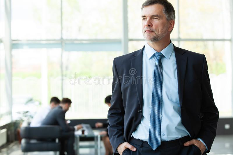 Modern mature businessman smiling and looking at camera with his colleagues in the background at office. stock image