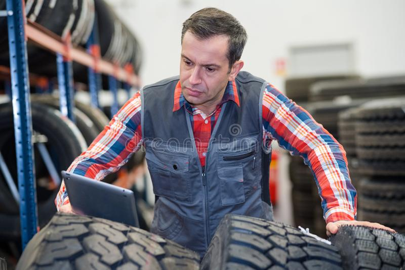 Modern mechanic using tablet to check tires stock photos