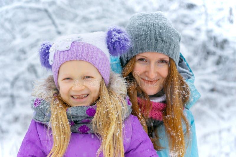 Modern med att le dottern på en vinter går royaltyfria foton