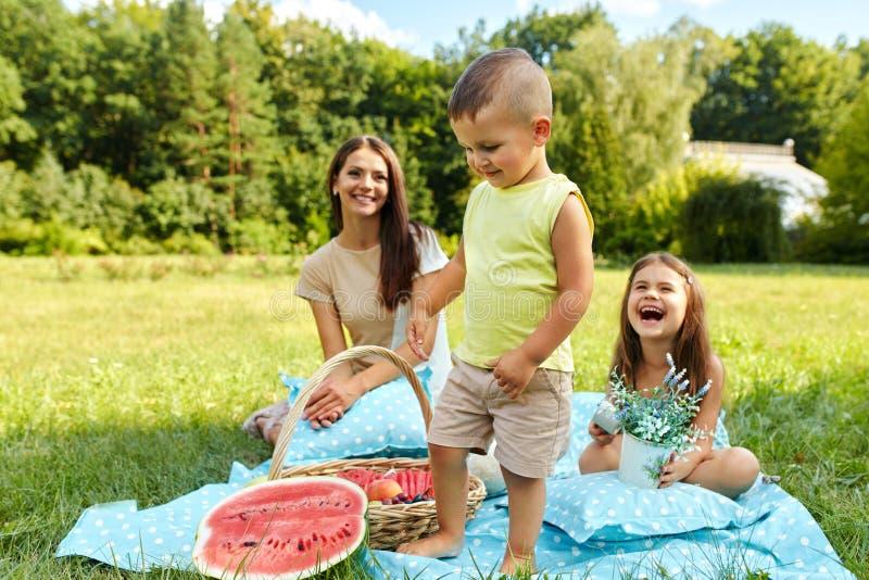 Modern med barn som har gyckel parkerar in lycklig familj utomhus royaltyfria foton