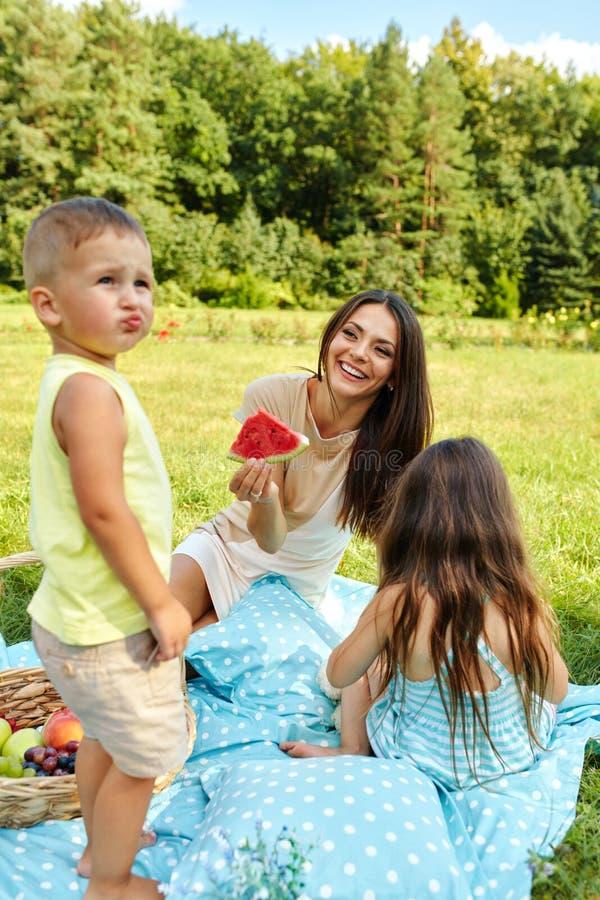 Modern med barn som har gyckel parkerar in lycklig familj utomhus royaltyfri bild