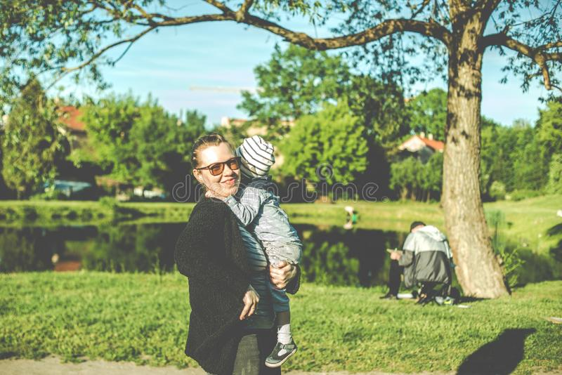 Modern med barnet i sommar parkerar royaltyfri bild