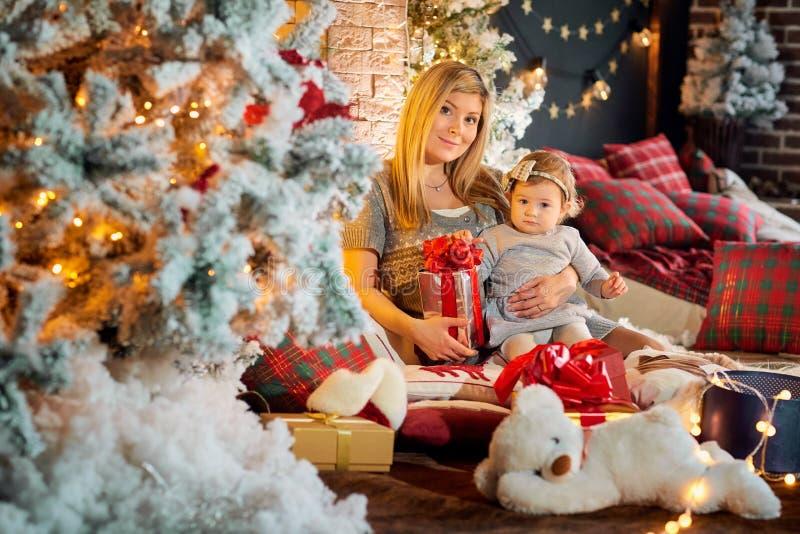 Modern med behandla som ett barn i en hatt av Santa Claus i julrummet arkivbild