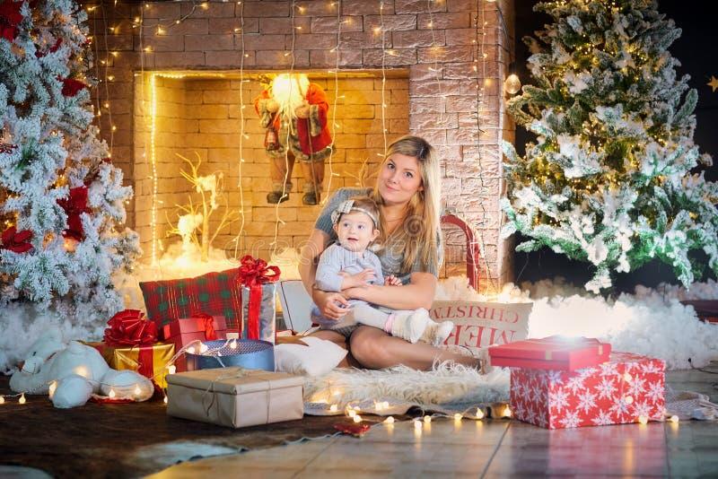 Modern med behandla som ett barn i en hatt av Santa Claus i julrummet royaltyfri bild