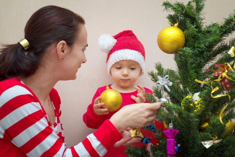 Modern med behandla som ett barn nära julgranen arkivbilder