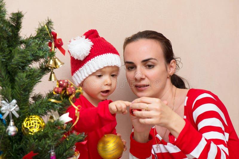 Modern med behandla som ett barn nära julgranen arkivfoto