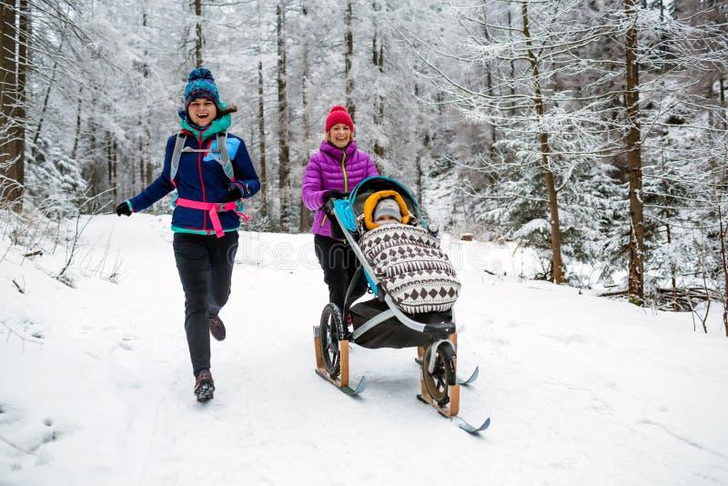 Modern med behandla som ett barn sittvagnen som tycker om vintern i skog, familjtid fotografering för bildbyråer