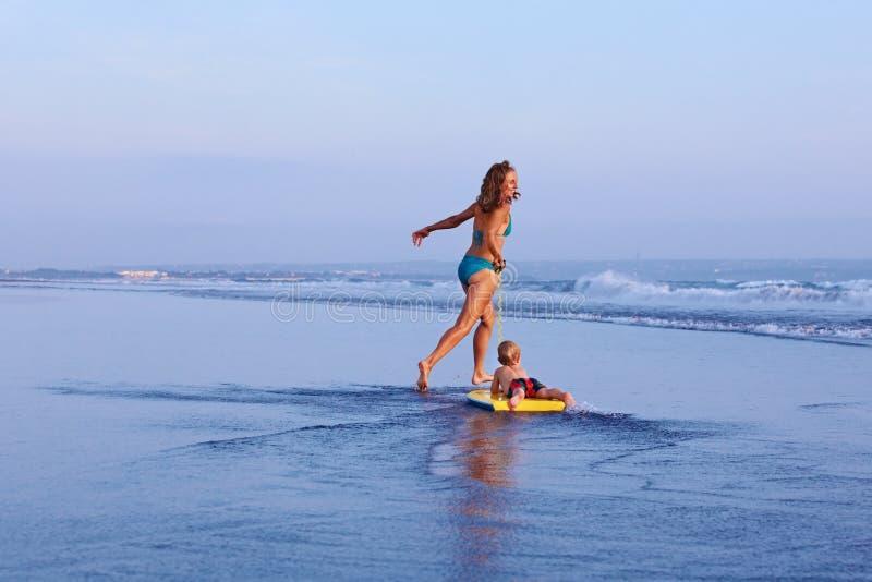 Modern med behandla som ett barn sonen på surfingbrädakörning längs stranden arkivfoton