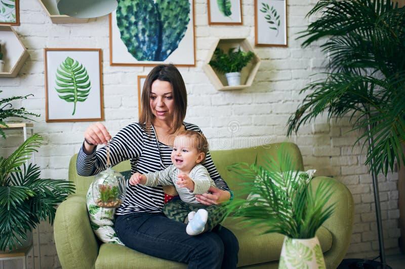 Modern med en årig 1 behandla som ett barn att sitta på en soffa hemma arkivfoto