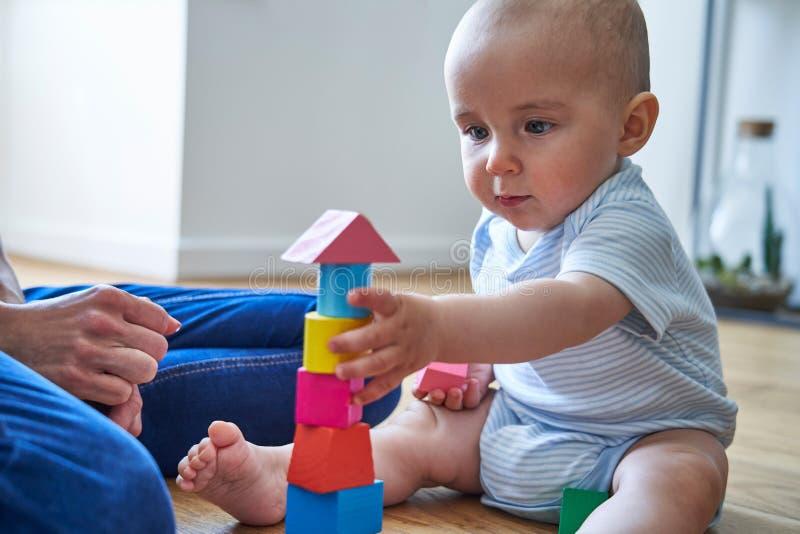 Modern med 8 gamla månad behandla som ett barn sonen som lär till och med att spela med färgade träkvarter hemma royaltyfria foton