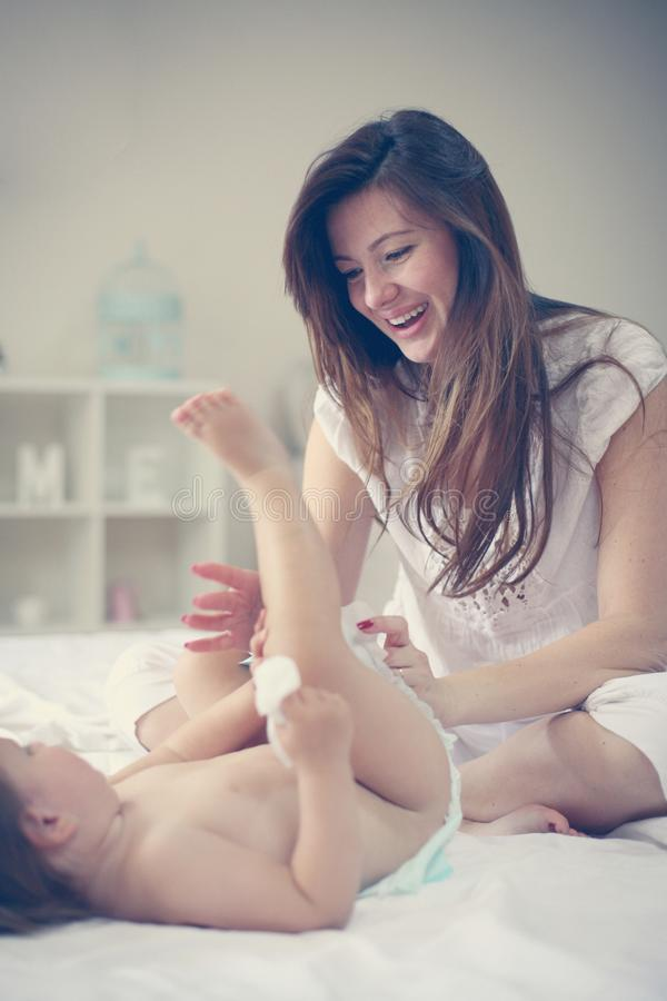 Modern med henne behandla som ett barn hemma Ändrande blöja för moder hennes litet arkivfoton