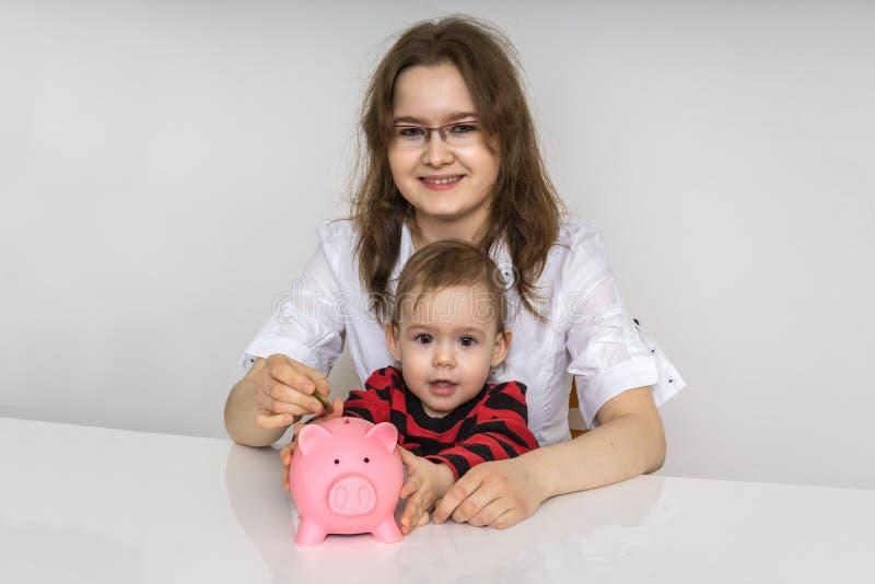 Modern med hennes barn rymmer piggy med besparingar arkivbilder