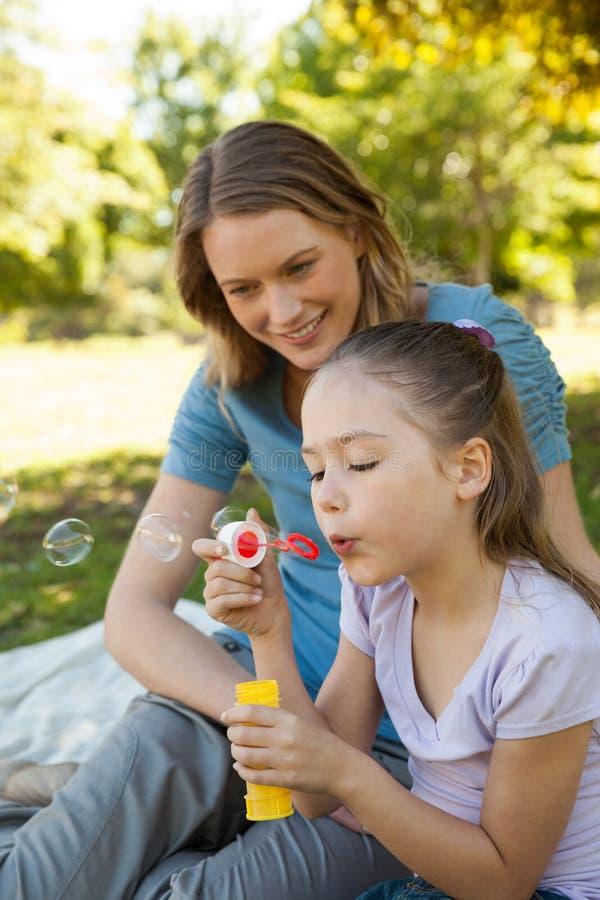 Modern med hennes dotter som blåser såpbubblor på, parkerar fotografering för bildbyråer