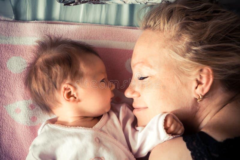 Modern med nyfött behandla som ett barn att sova arkivfoto