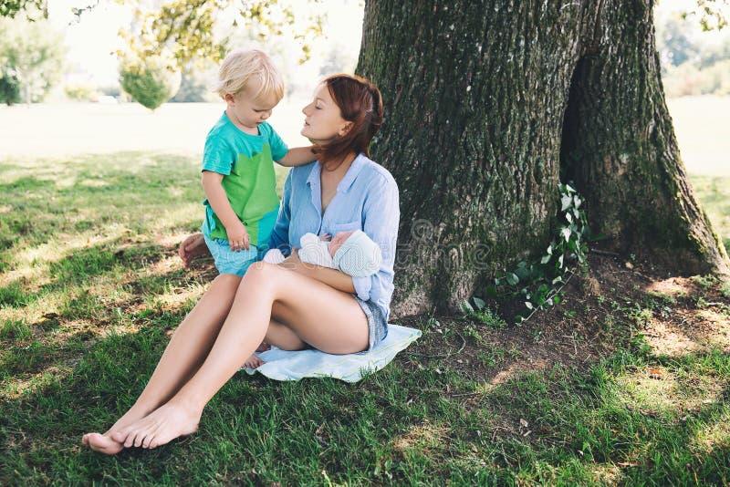 Modern med nyfött behandla som ett barn och äldre barn på naturen royaltyfri foto