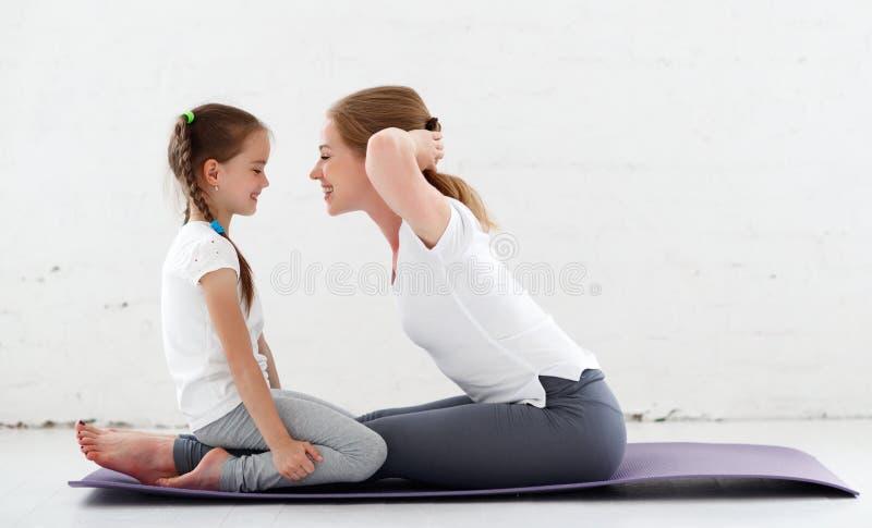 Modern med praktiserande yoga för barn i lotusblomma poserar arkivbilder