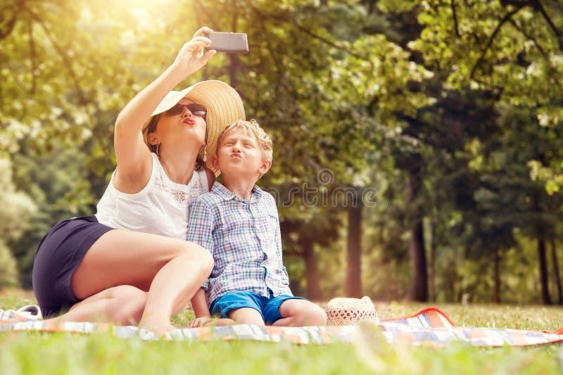 Modern med sonen tar ett selfiefoto royaltyfri fotografi
