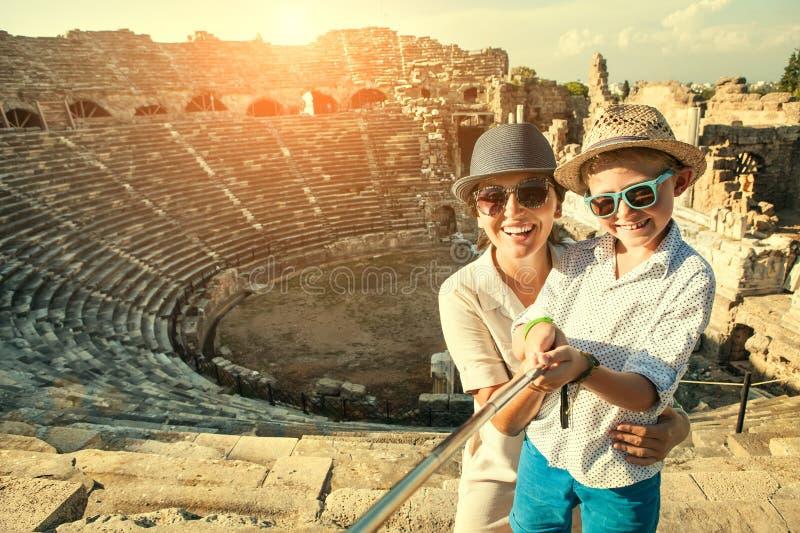 Modern med sonen tar ett selfiefoto i antik teater arkivfoton