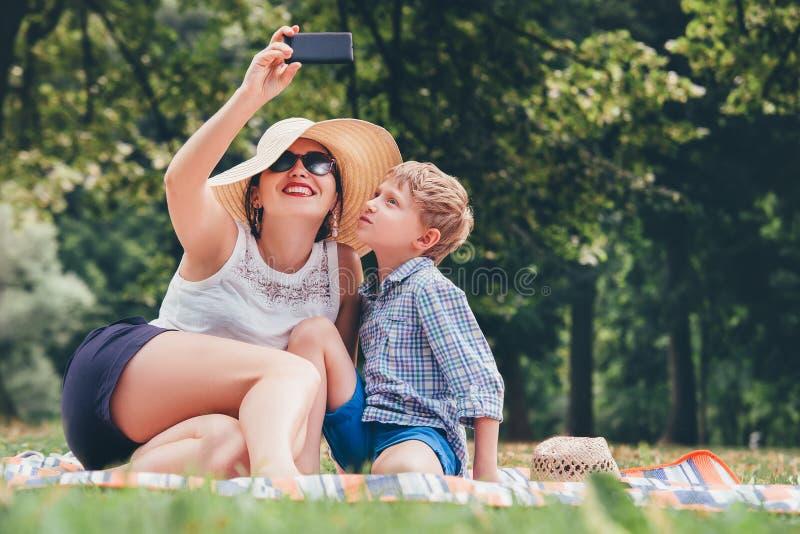 Modern med sonen tar ett selfiefoto i sommar parkerar royaltyfria foton