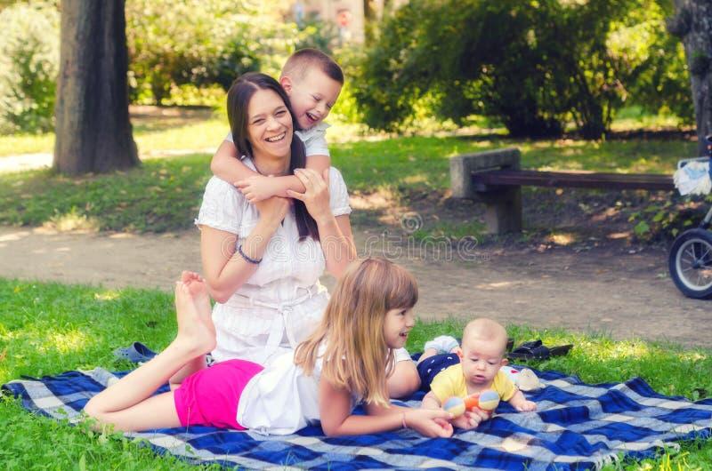 Modern med tre barn som spelar i sommaren, parkerar royaltyfri bild
