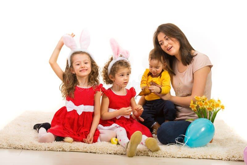 Modern med tre ungar firar påsk arkivbilder