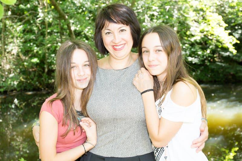 Modern med två kopplar samman dottertonåringflickor arkivfoto