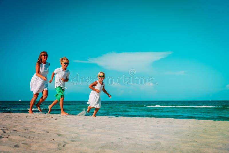 Modern med ungar spelar körning på den tropiska stranden royaltyfria foton