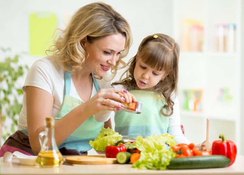 Modern med ungen gör sallad arkivbild
