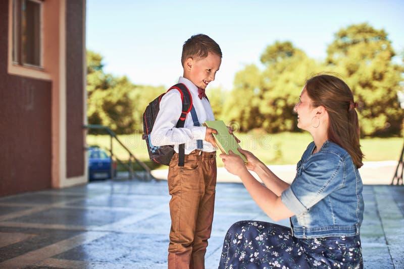 Modern medföljer barnet till skola mamman uppmuntrar studenten som medföljer honom till skola en att bry sig moder ser ömt på hen arkivfoton