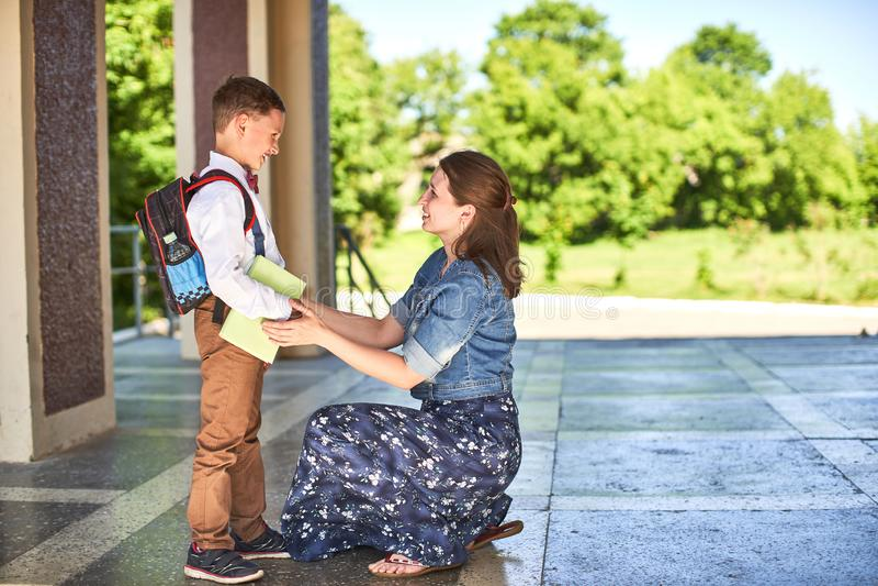 Modern medföljer barnet till skola mamman uppmuntrar studenten som medföljer honom till skola en att bry sig moder ser ömt på hen royaltyfri foto