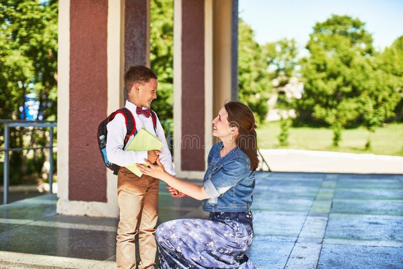Modern medföljer barnet till skola mamman uppmuntrar studenten som medföljer honom till skola en att bry sig moder ser ömt på hen royaltyfri fotografi