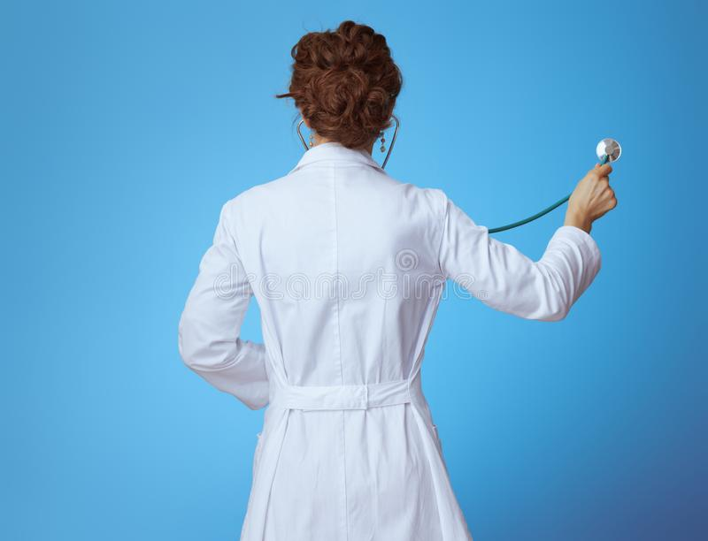 Modern medical doctor woman listening with stethoscope on blue. Seen from behind modern medical doctor woman in bue shirt, red pants and white medical robe royalty free stock photo
