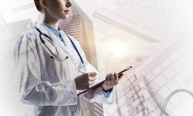 Modern medical industry concept. Side view of confident woman doctor in white medical uniform holding notebook and pen in hands while standing against city view royalty free illustration