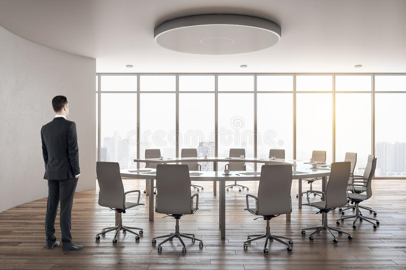 Modern meeting room interior. Thoughtful businessman standing in modern meeting room interior with city view, copy space and daylight. Workplace concept royalty free stock image