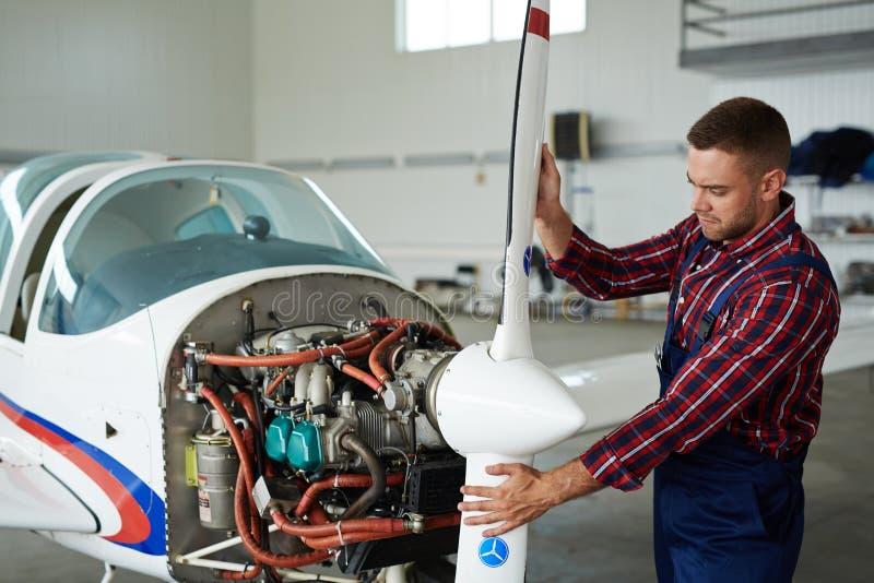 Modern mekaniker Repairing Jet Plane royaltyfri fotografi