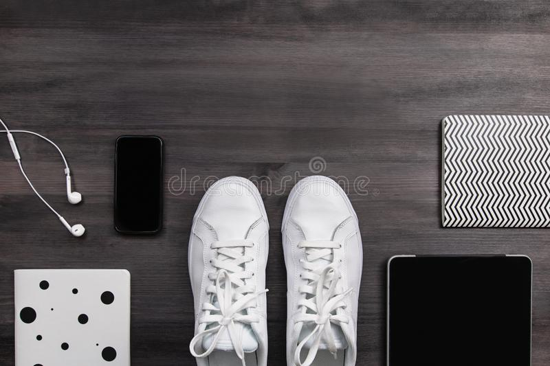 Modern men fashion accessories and electronic devices on dark background. White sneakers, tablet and phone flat lay. Modern men fashion accessories and stock image