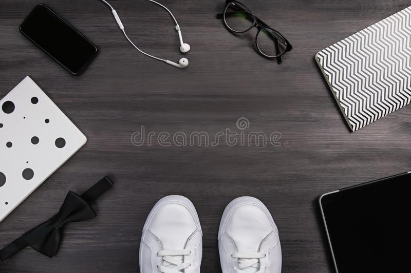 Modern men fashion accessories and electronic devices on dark background. White sneakers, tablet and phone flat lay. Modern men fashion accessories and stock photos