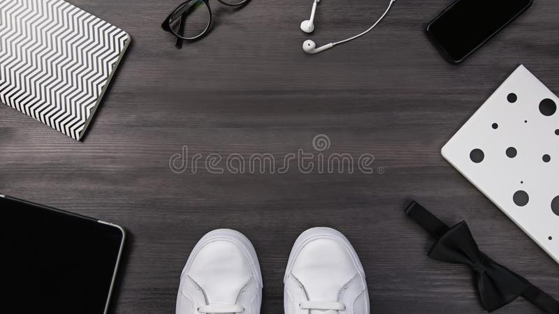 Modern men fashion accessories and electronic devices on dark background. White sneakers, tablet and phone flat lay. Modern men fashion accessories and stock photography