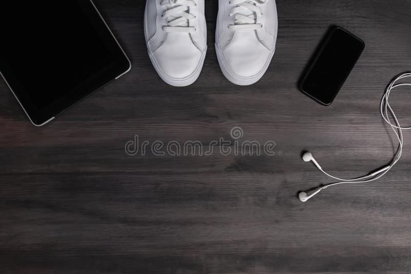 Modern men fashion accessories and electronic devices on dark background. White sneakers, tablet and phone flat lay. Modern men fashion accessories and royalty free stock images