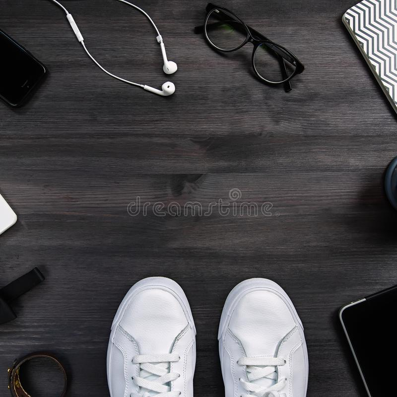 Modern men fashion accessories and electronic devices on dark background. White sneakers, tablet and phone flat lay. Modern men fashion accessories and royalty free stock photography