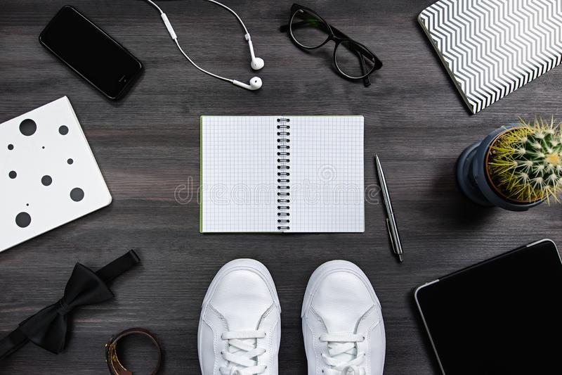 Modern men fashion accessories and electronic devices on dark background. White sneakers, tablet and phone flat lay. Modern men fashion accessories and royalty free stock image