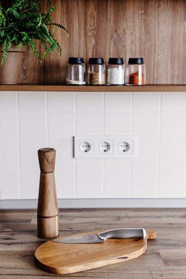 Modern mes op houten scherpe raad met peperkruid op houten lijstbovenkant Het koken op moderne keuken met meubilair in grijze kle stock fotografie