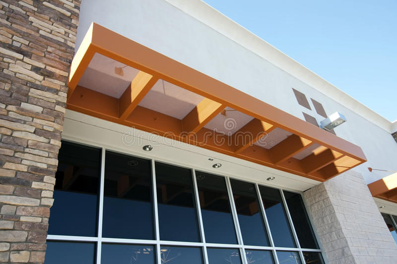 Modern metal awning over storefront. Modern perforated metal awning partially shades visitors of this building from the blistering hot Arizona sun stock photography